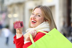Shopper showing a blank credit card and holding shopping bags in winter outdoors on the street